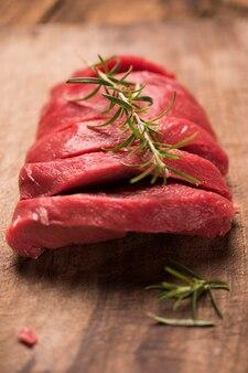 Steak de boeuf cru sur une table en bois sombre.