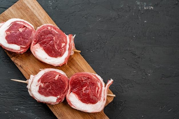 Steak de boeuf cru sur une table en bois sombre