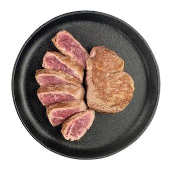 Steak de boeuf cuit frit coupé en morceaux dans une poêle en fonte isolée sur fond blanc. vue de dessus.