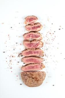 Steak de boeuf cuit frit coupé en morceaux avec des épices sur fond blanc. vue de dessus.