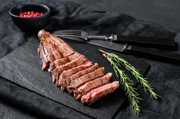 Steak de bœuf flanc rôti moyen rare. fond noir. vue de dessus