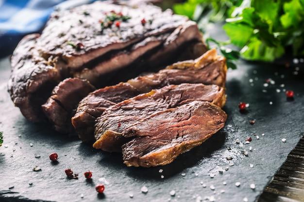 Steak de boeuf fraîchement grillé sur plaque d'ardoise avec sel poivre romarin et herbes de persil. morceaux tranchés de steak de boeuf juteux.