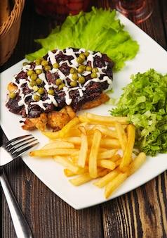 Steak de boeuf avec frites, salade verte, haricots verts et pépites de poulet.