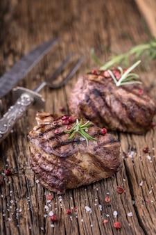 Steak de boeuf grillé au romarin, sel et poivre sur une vieille planche à découper. steak de filet de boeuf.