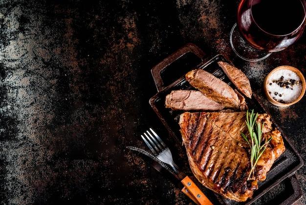 Steak de boeuf grillé aux épices sur une plaque de cuisson avec un verre de vin rouge