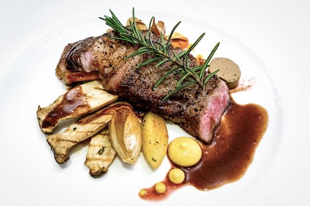 Steak de bœuf grillé aux herbes sur plaque blanche
