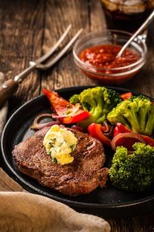 Steak de boeuf grillé avec beurre à l'ail et légumes. viande au poivron grillé, brocoli et oignons.