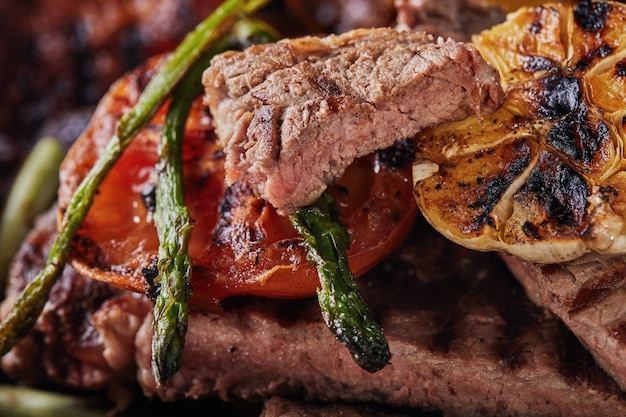 Steak de boeuf grillé dans une poêle noire avec des légumes au four - tomates, asperges, ail et poivrons