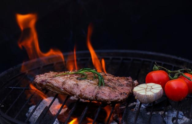 Steak de boeuf sur la grille du gril, flammes sur le fond