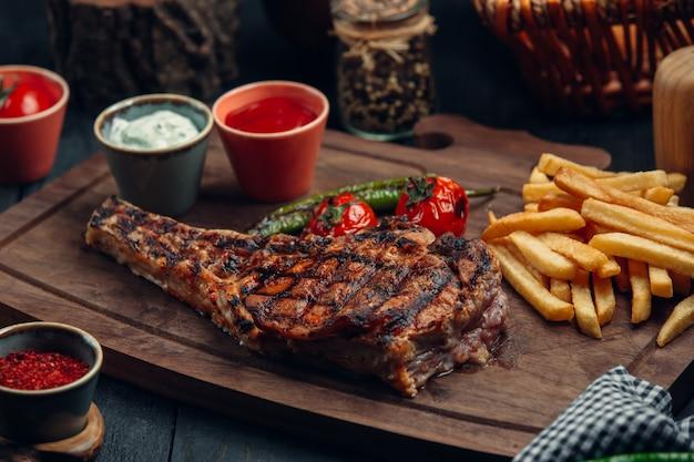 Steak de boeuf grillé avec frites, tomates grillées, poivrons et sauces