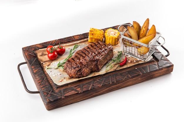 Steak de boeuf grillé isolé sur la planche de bois avec des quartiers de pommes de terre, maïs et tomates