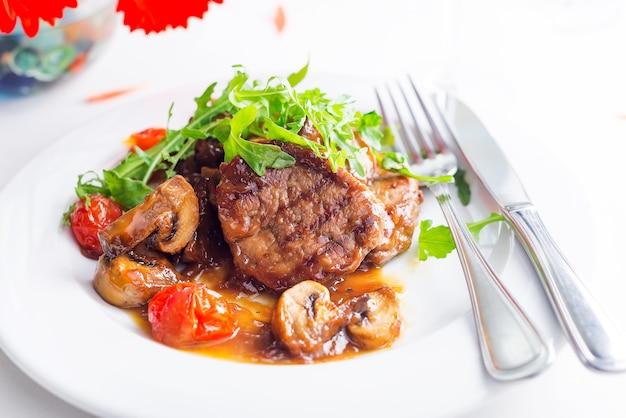 Steak de boeuf grillé et légumes avec du vin et des fleurs sur une surface blanche