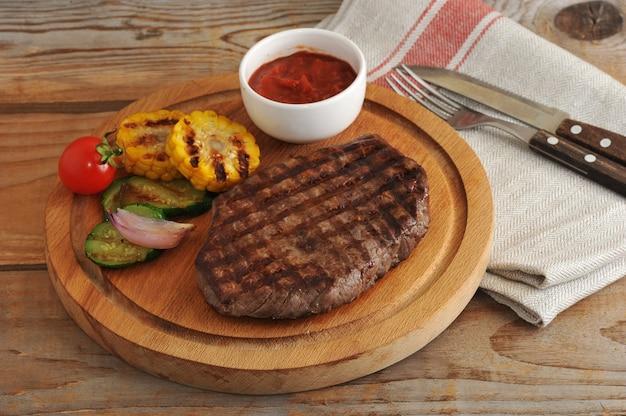 Steak de bœuf grillé, légumes grillés - courgettes, maïs, oignons, ail, cerises