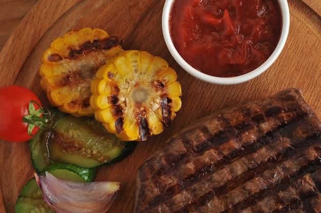 Steak de bœuf grillé, légumes grillés - courgettes, maïs, oignons