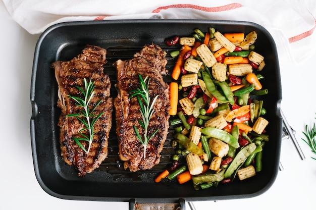 Steak de boeuf grillé avec légumes et romarin dans une poêle noire sur la table.