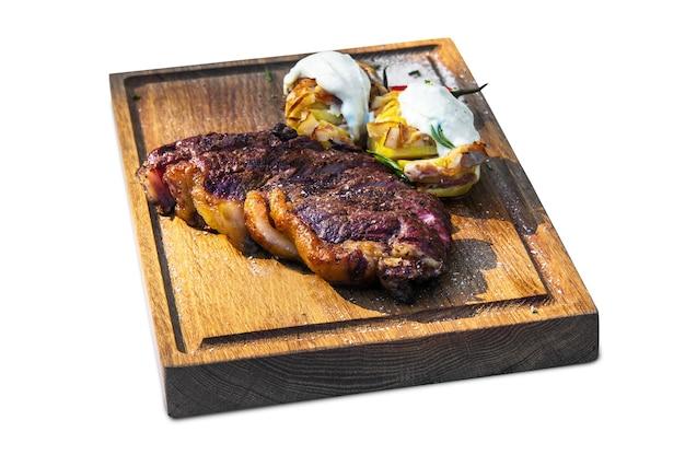 Steak de boeuf grillé sur planche de bois sur fond blanc isolé