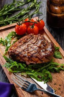 Steak de boeuf grillé sur une planche à découper en bois.