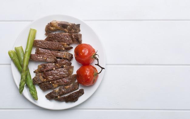 Steak de boeuf grillé sur une plaque blanche et fond blanc, plat et espace copie