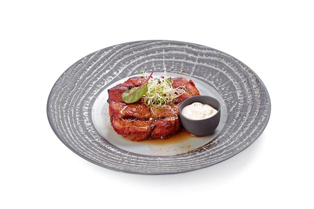Steak de boeuf grillé sur plaque grise isolé
