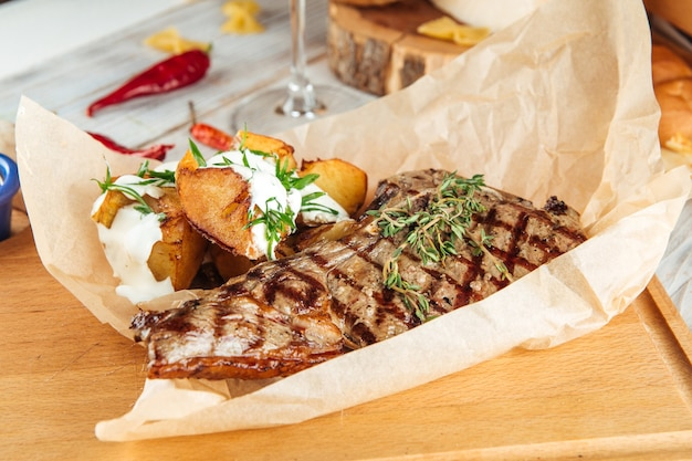 Steak de boeuf grillé avec pommes de terre sur la planche de bois