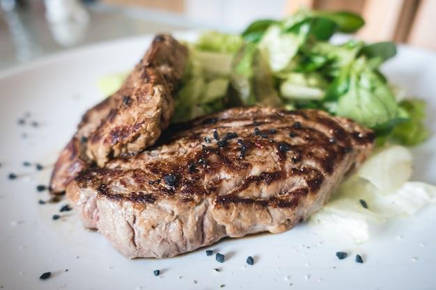 Steak de boeuf grillé avec salade côté jardin