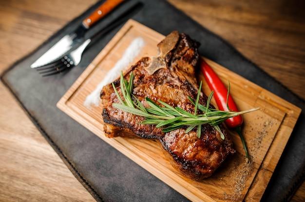 Steak de boeuf grillé sur une table en bois sombre.