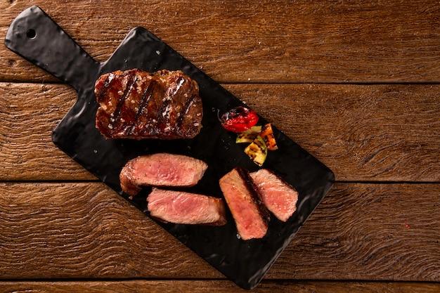 Steak de boeuf grillé en tranches sur une planche à découper noire sur la table en bois.