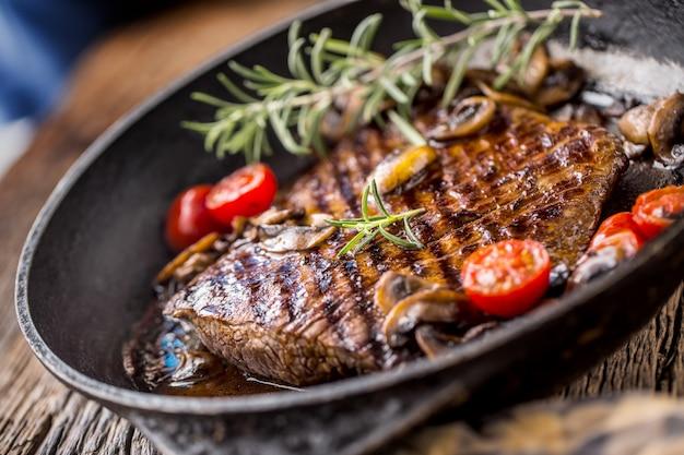 Steak de bœuf. griller le bifteck de flanc de bœuf avec les champignons au romarin et les tomates dans une poêle.