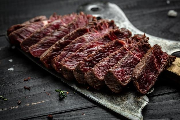 Steak de boeuf juteux sur couteau de boucher à viande. fond de recette de nourriture. fermer