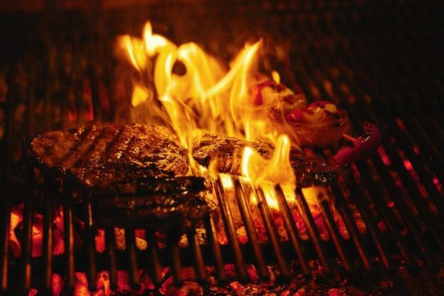 Steak de boeuf juteux dans une flamme de barbecue