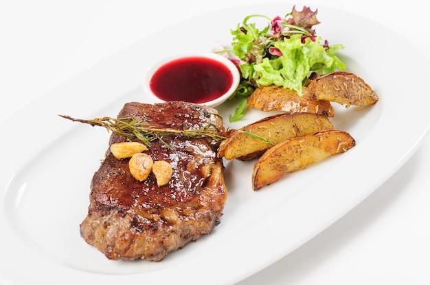 Steak de bœuf juteux épais avec pomme de terre et salade
