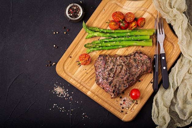 Steak de bœuf juteux rare aux épices sur une planche de bois et garniture d'asperges. mise à plat. vue de dessus
