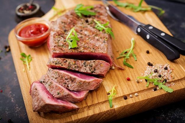 Steak de bœuf juteux rare aux épices sur une planche de bois