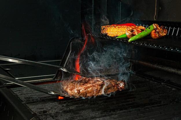 Le steak de boeuf et les légumes sont grillés et retournés avec des pinces. la photo montre des flammes et de la fumée. fermer.