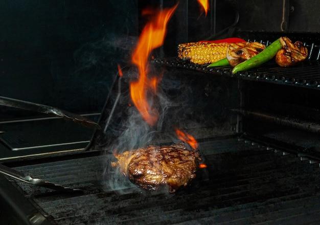 Steak de boeuf et légumes sont grillés et retournés avec des pinces