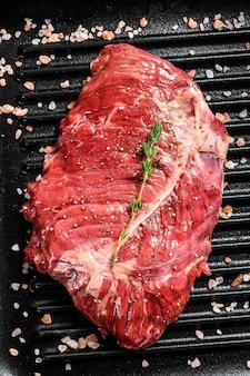 Steak de boeuf marbré cru sur une lèchefrite