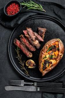 Steak de bœuf marbré avec garniture de patates douces au four. viande grillée