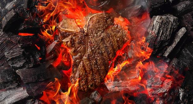 Steak de boeuf marbré grillé avec des charbons et de la fumée