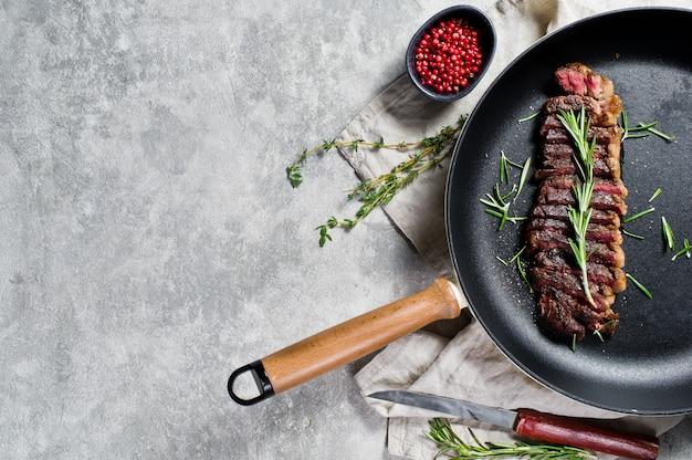 Steak de boeuf en marbre noir angus à rôtir dans une poêle.