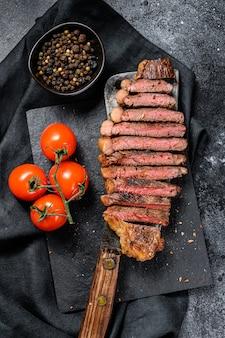 Steak de bœuf marbré en tranches grillé sur un couperet à viande. surface noire. vue de dessus