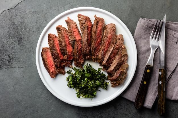 Steak de boeuf moyen sur une plaque blanche