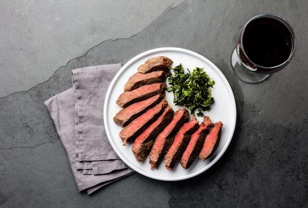 Steak de bœuf sur une plaque blanche avec un verre de vin rouge