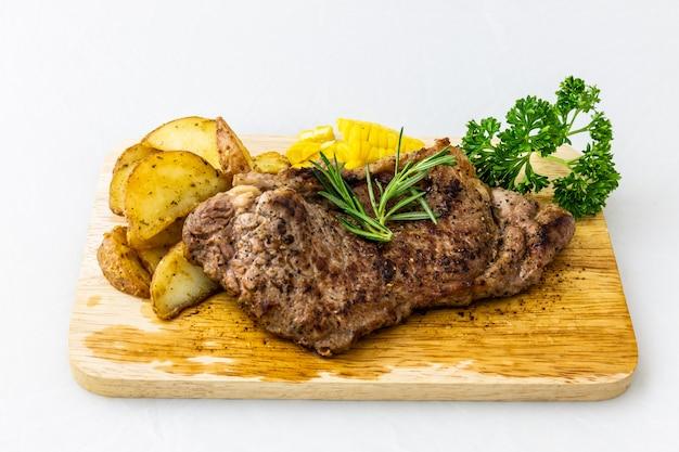 Steak de boeuf sur un plateau en bois avec pommes de terre et persil, romarin, maïs sur blanc