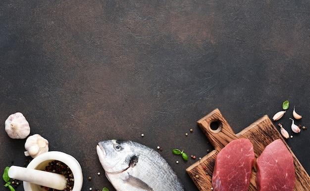 Steak de boeuf et poisson dorado aux épices et ail sur fond de béton.