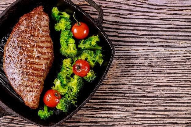 Steak de boeuf saignant grillé avec brocoli et tomate sur une poêle à griller sur fond de bois.