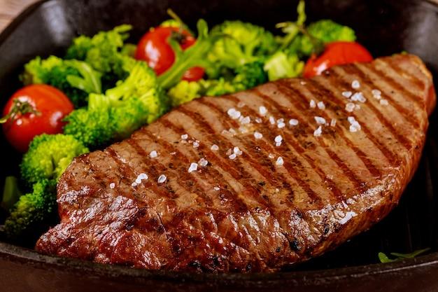 Steak de bœuf saignant moyen grillé avec brocoli et tomate sur une lèchefrite. fermer.
