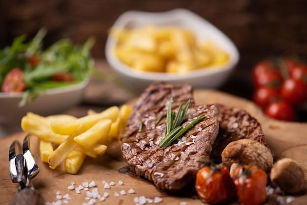 Steak de bœuf saignant moyen grillé tranché servi avec frites en gros plan