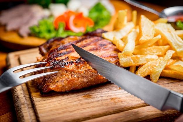 Steak de boeuf avec sauce au poivre et légumes grillés sur une planche à découper