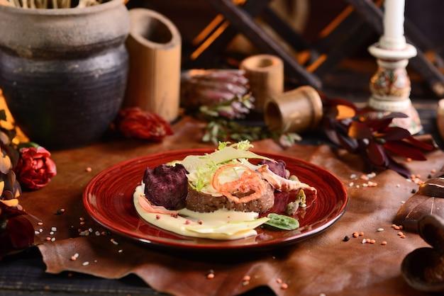 Steak de boeuf avec sauce à la crème avec un décor de légumes. sur la plaque rouge