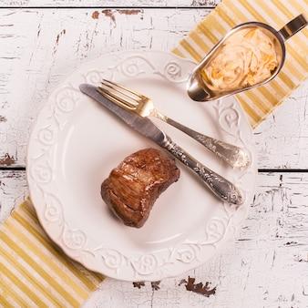 Steak de boeuf avec sauce à l'oignon sur une table en bois blanche.